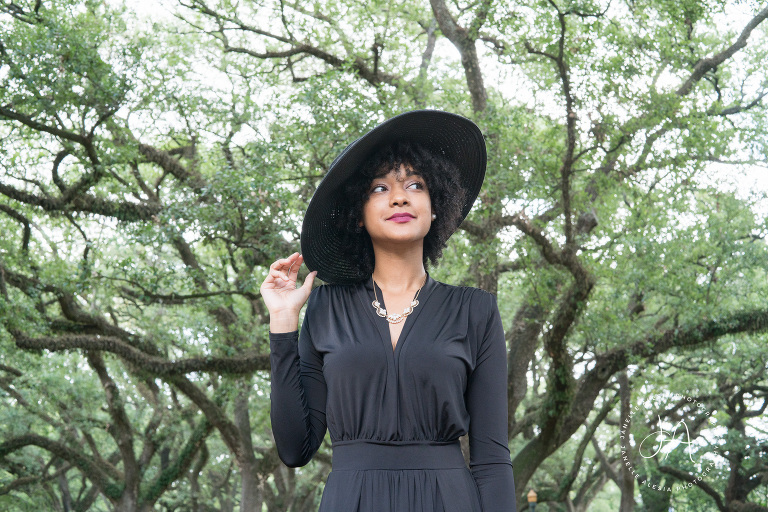 black woman in nature holding black hat on her head
