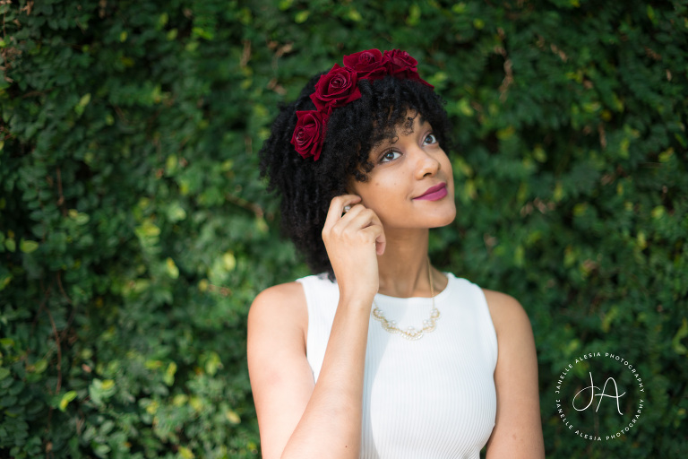 natural hair woman with flower crown in front of ivy wall