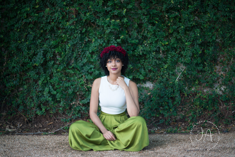 natural hair woman sitting in front of ivy walll